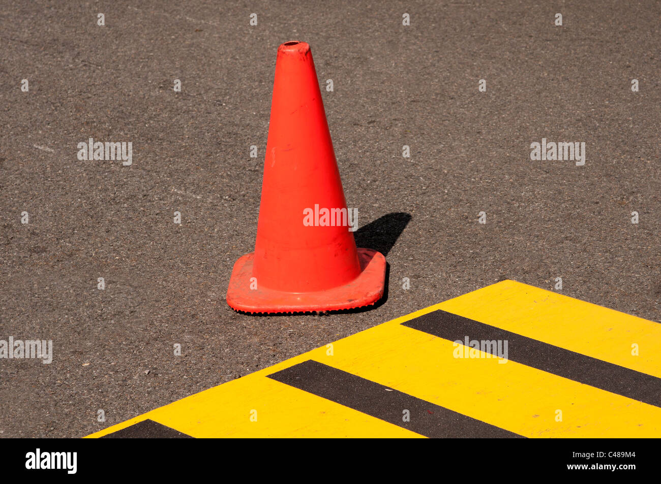 Orange traffic cone at crosswalk. - Stock Image