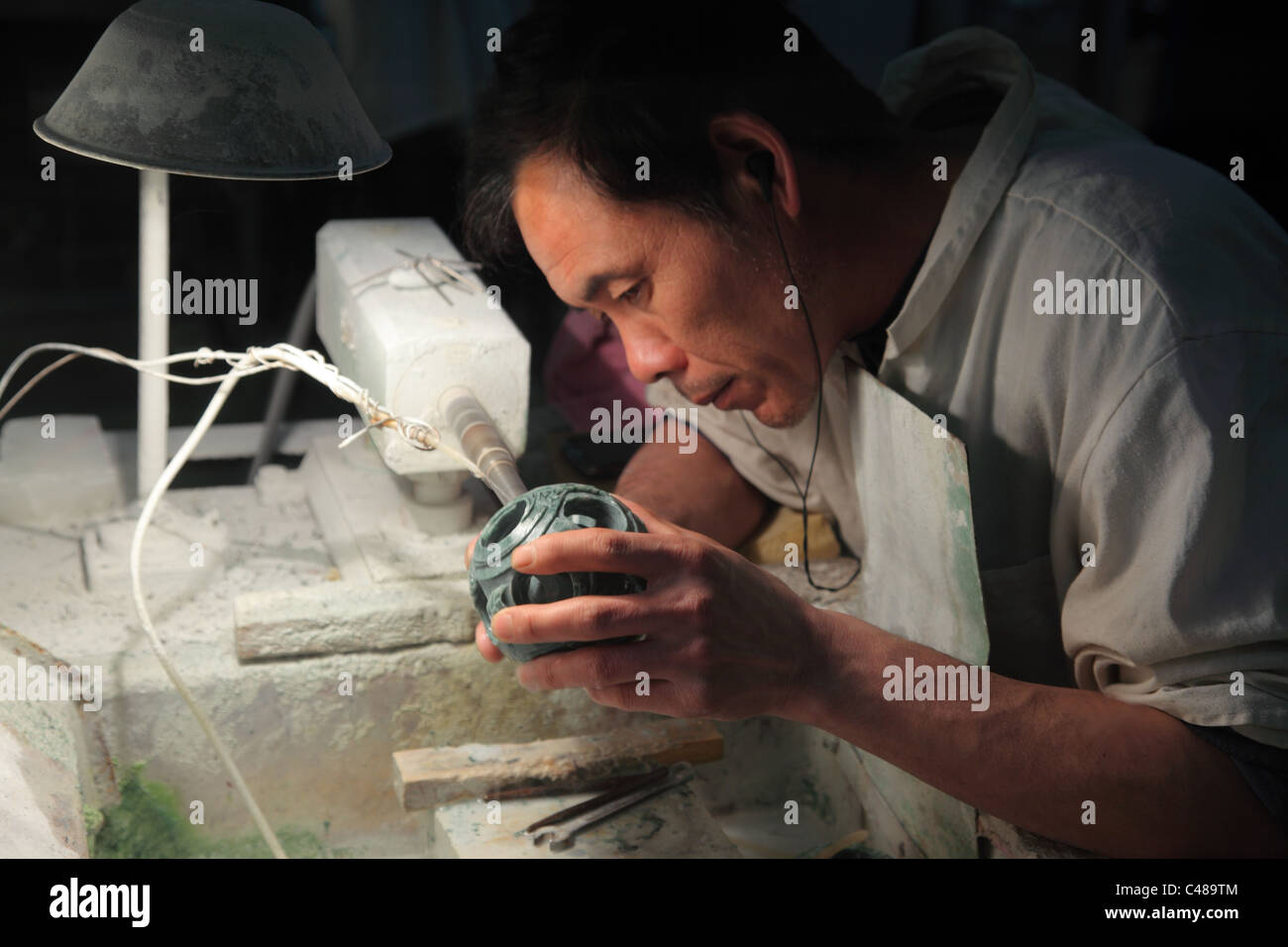 Chinese worker in factory carving jade sculpture, Beijing, China - Stock Image