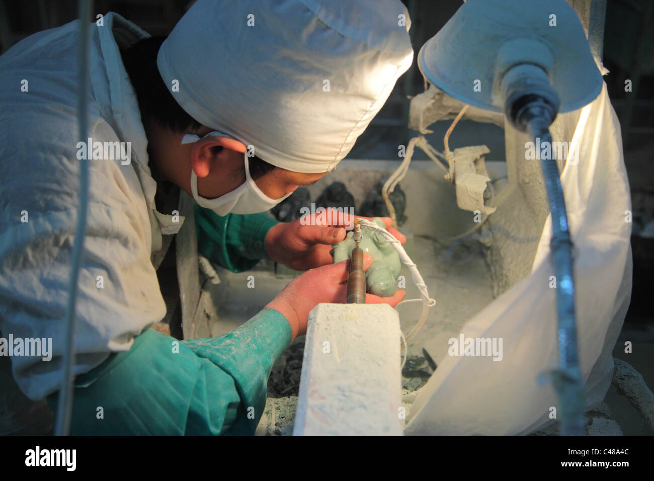 Chinese worker in factory carving jade Buddha sculpture, Beijing, China - Stock Image