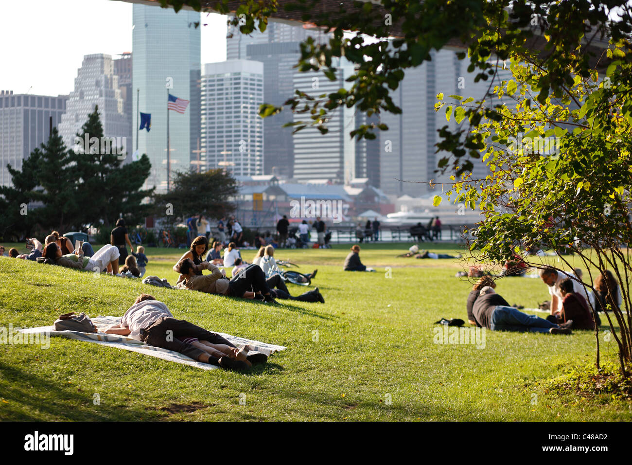 People lying on the grass under the Brooklyn Bridge, New York City, USA - Stock Image