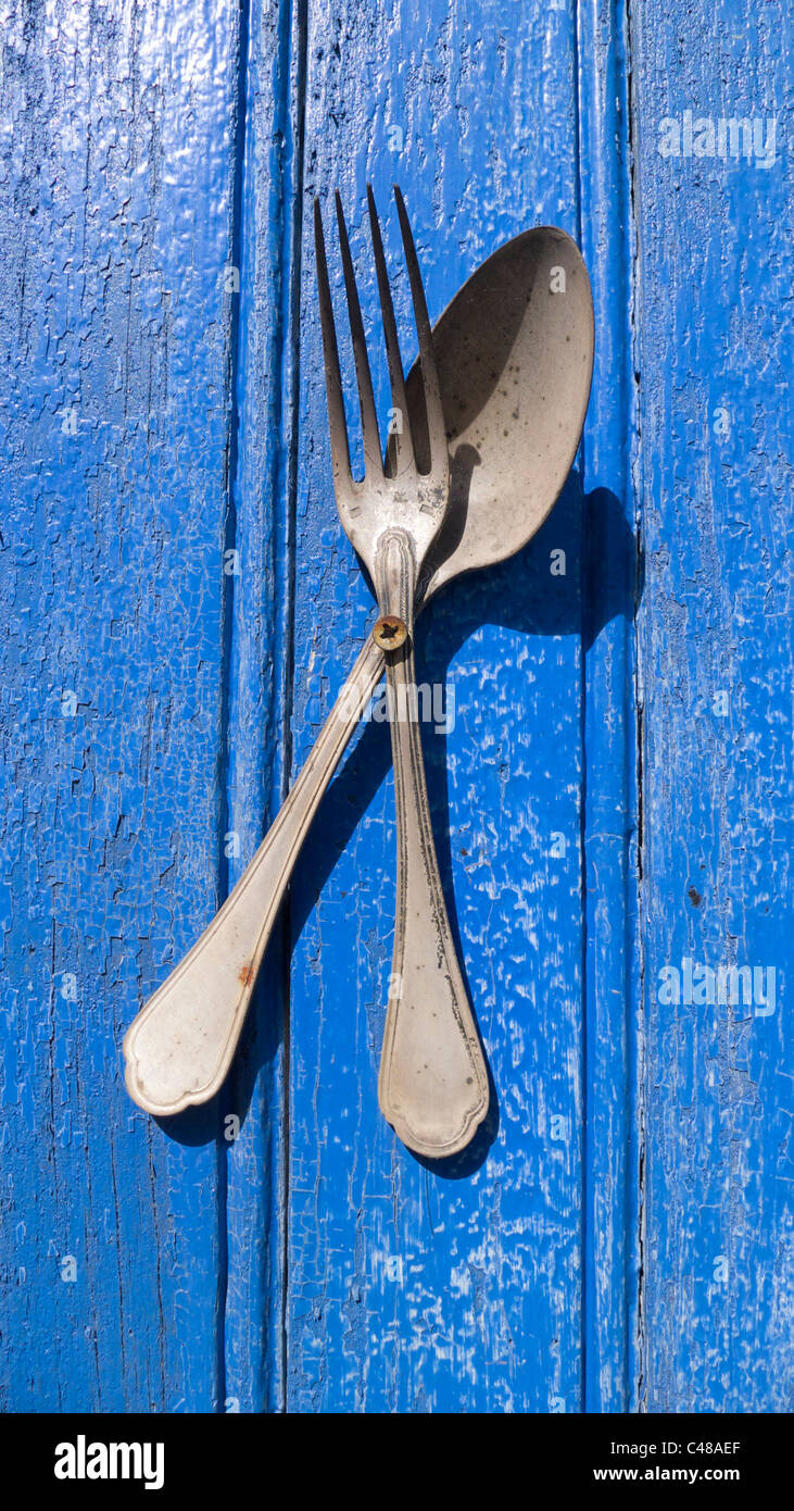 Fork and spoon attached to blue door advertising a Brocante (secondhand shop) in Bourganeuf, Limousin, France - Stock Image