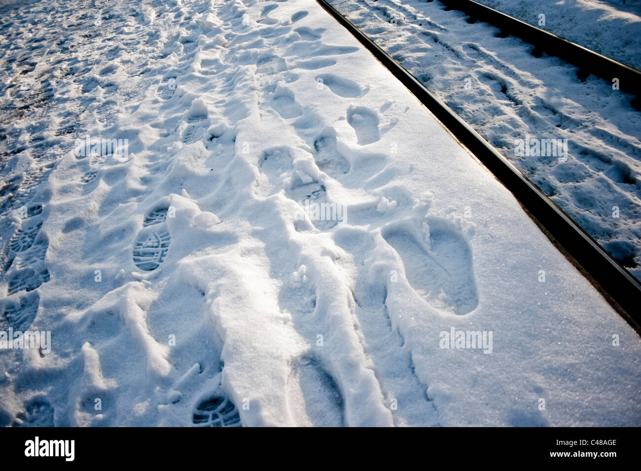 Evidence of a large number of passengers in the snow of a railway platform. - Stock Image