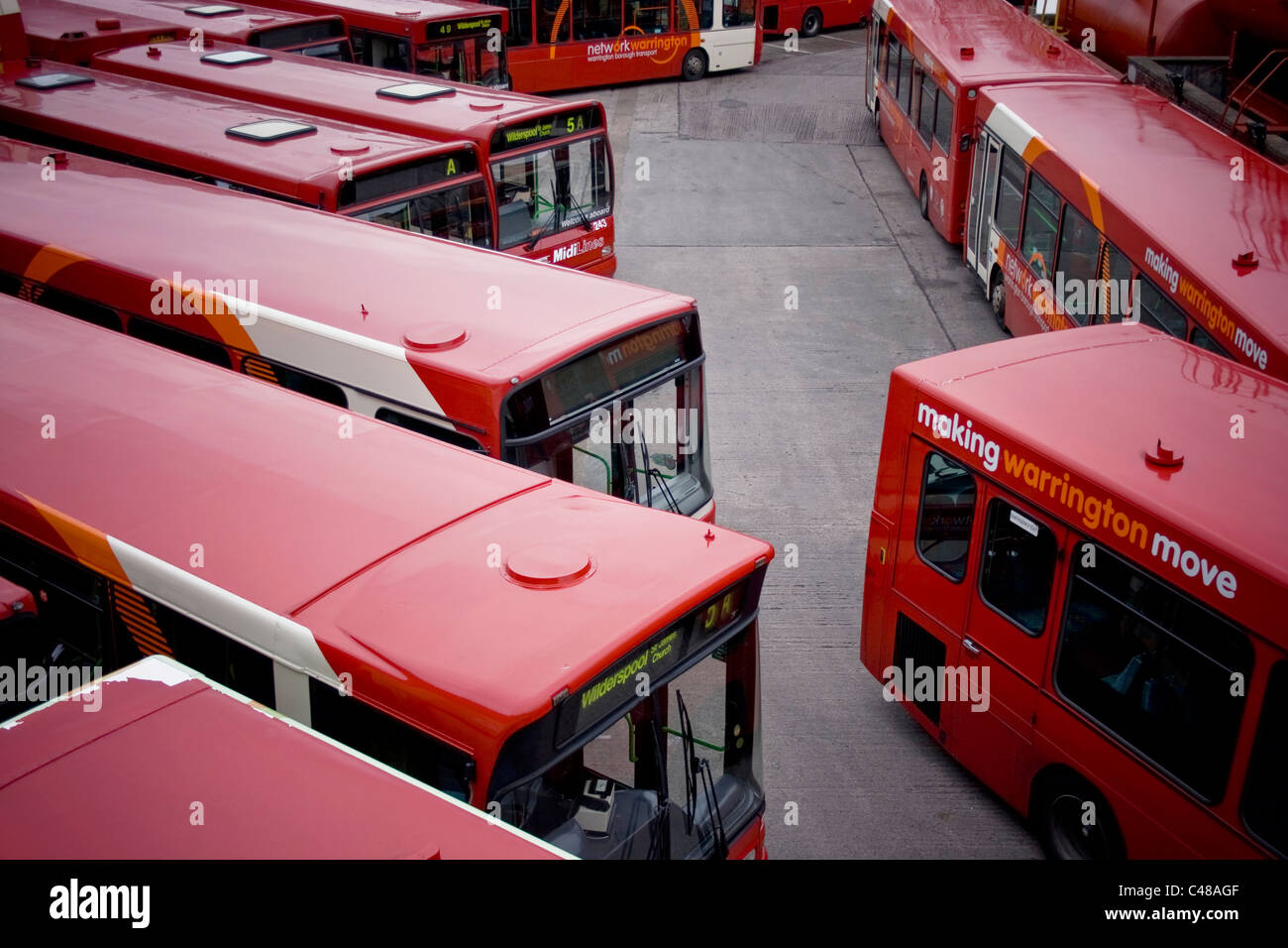 A number of Warrington buses sit parked in a depot during a public holiday. - Stock Image