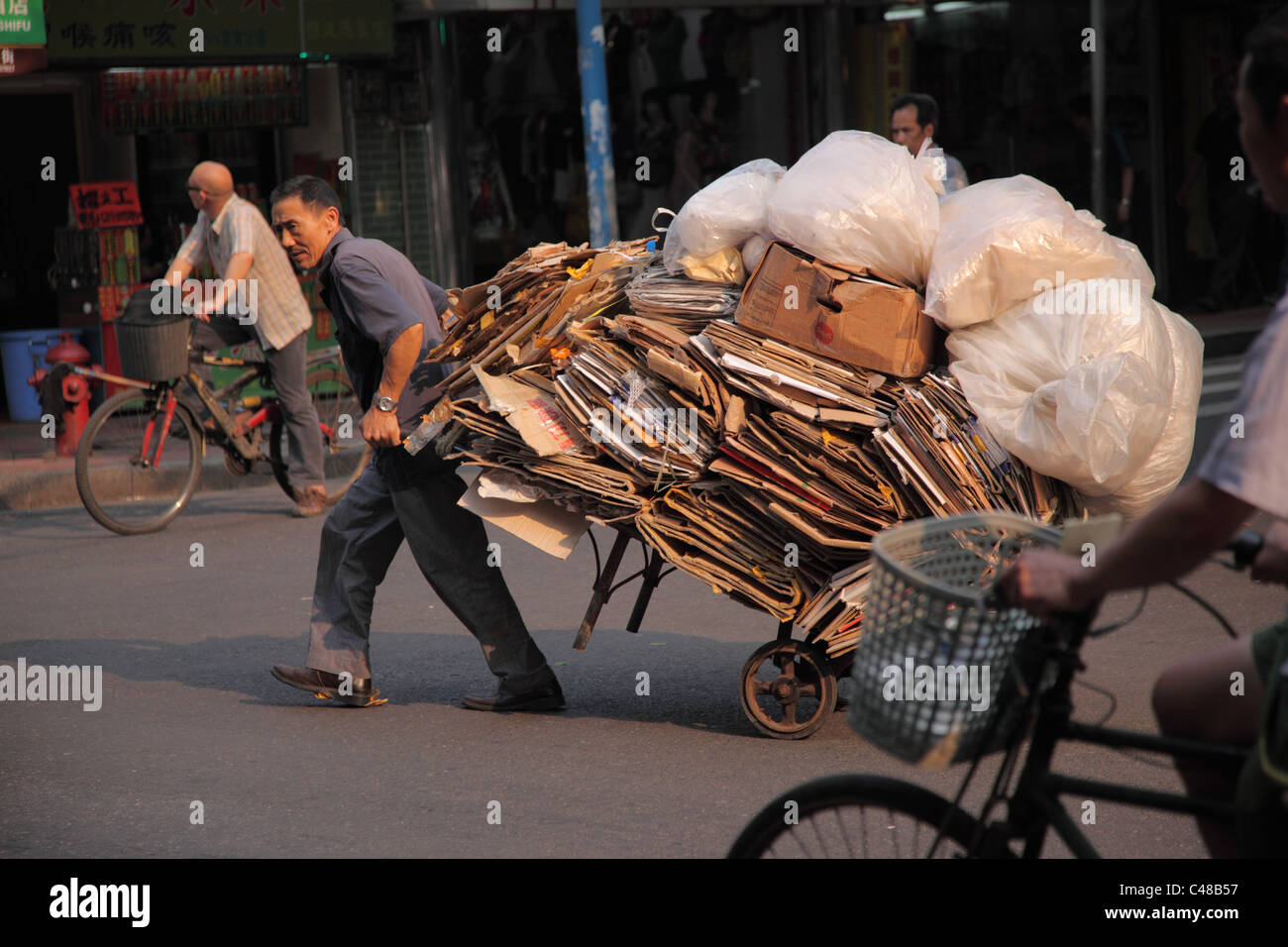 Man pulls cart full of recyclables, Guangzhou, China - Stock Image
