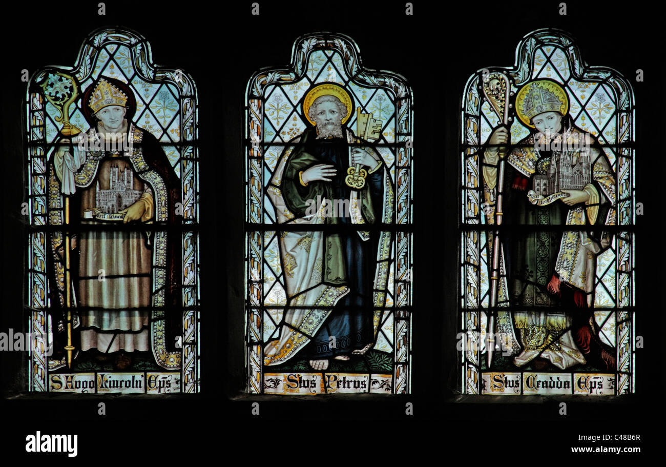 A stained glass window by The Kempe Studios depicting Saints Hugh of Lincoln, Peter and Chad - Stock Image