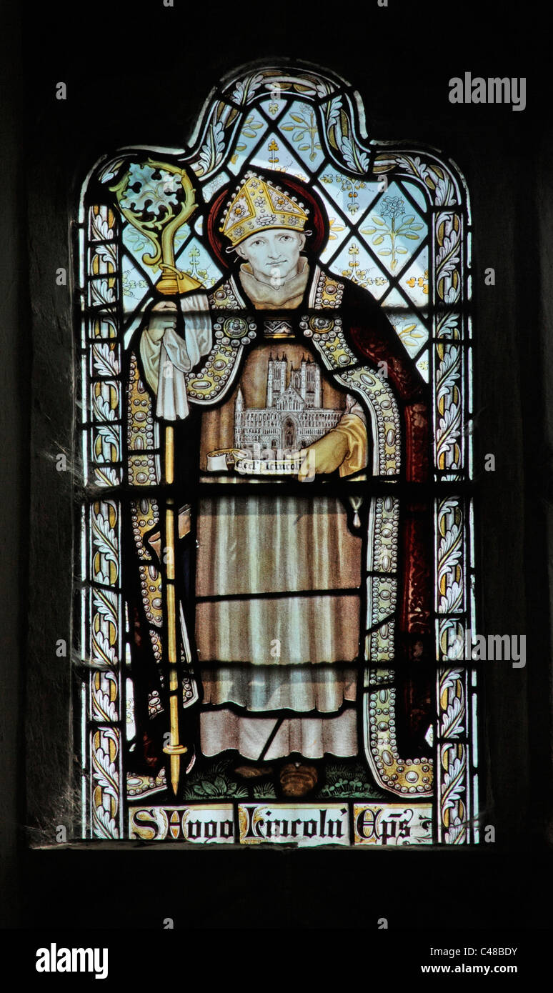 A stained glass window by The Kempe Studios depicting St Hugh of Lincoln - Stock Image