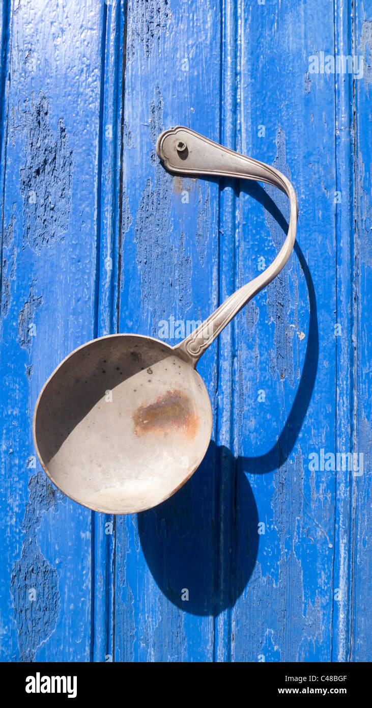 Bent spoon attached to blue door advertising a Brocante (secondhand shop) in Bourganeuf, Limousin, France - Stock Image