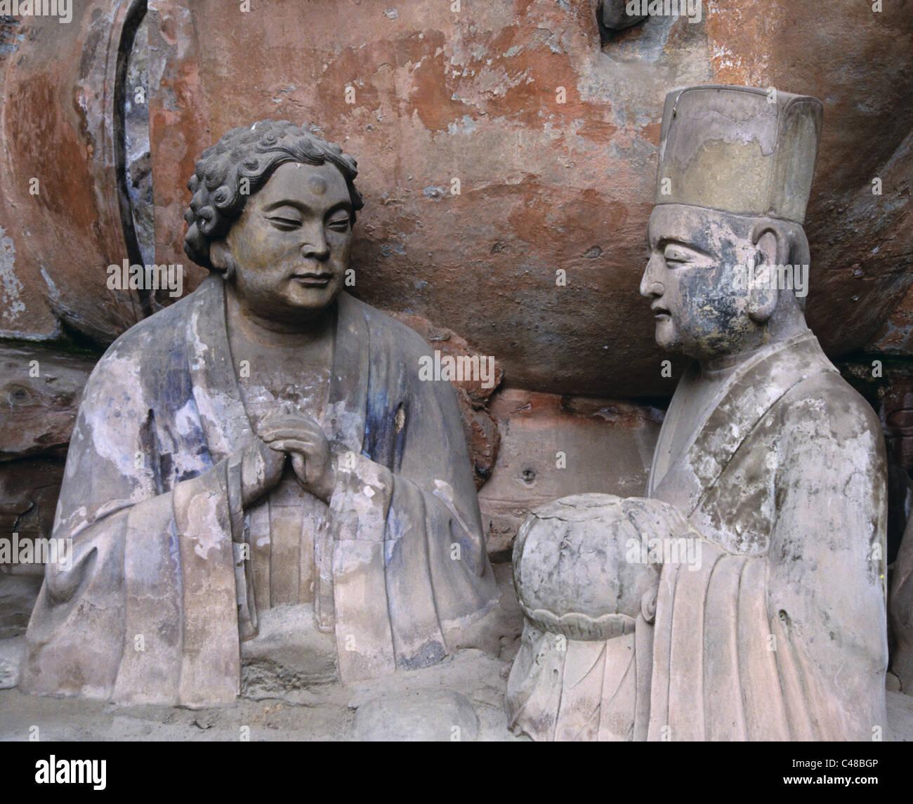 Curly headed figure by the Recumbent Buddha (1174-1252 AD), Baodingshan, Dazu, China 990603_1719 - Stock Image