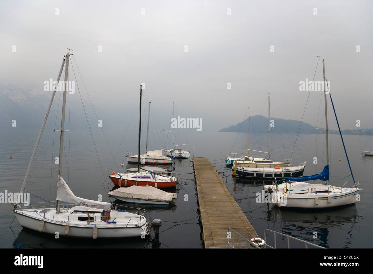 Moorage with boats against Lake Como at Tremezzo. Lombardy. Italy. Winter. - Stock Image