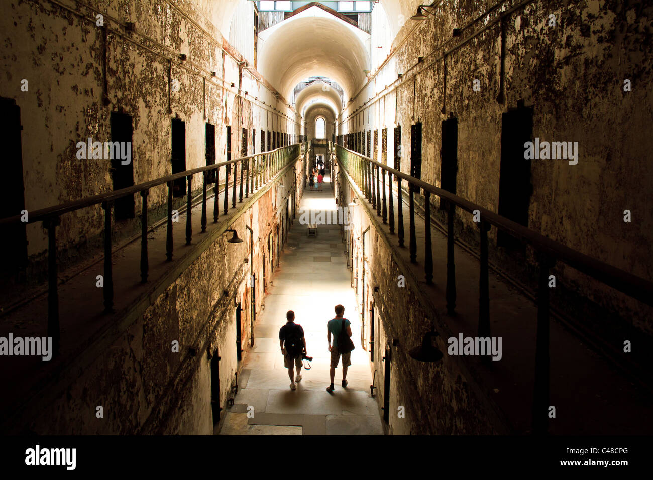 Tourists walk down a crumbling cellblock at Eastern State Penitentiary in Philadelphia, Pa. The prison is said to - Stock Image