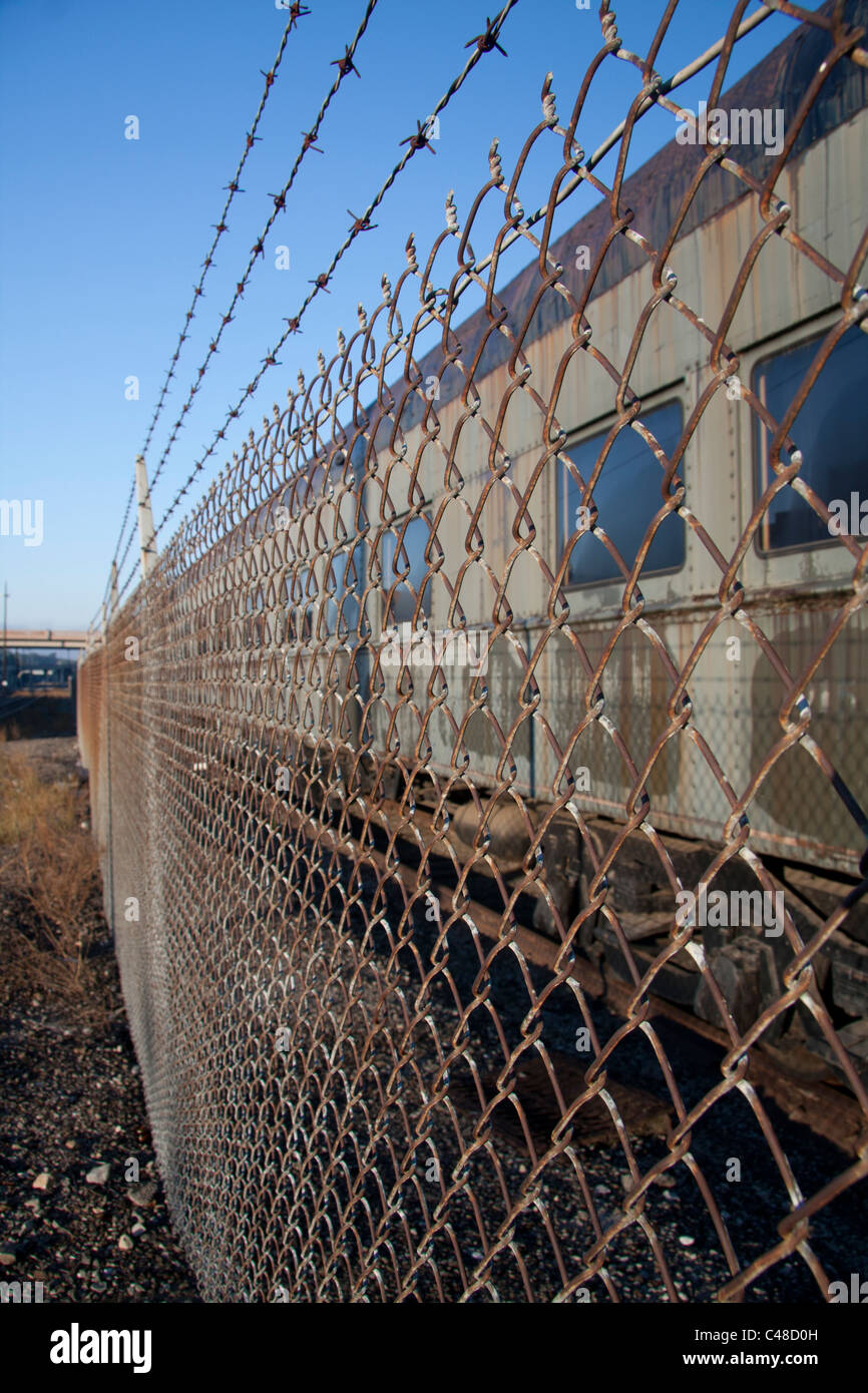 train behind barbed wire fence - Stock Image