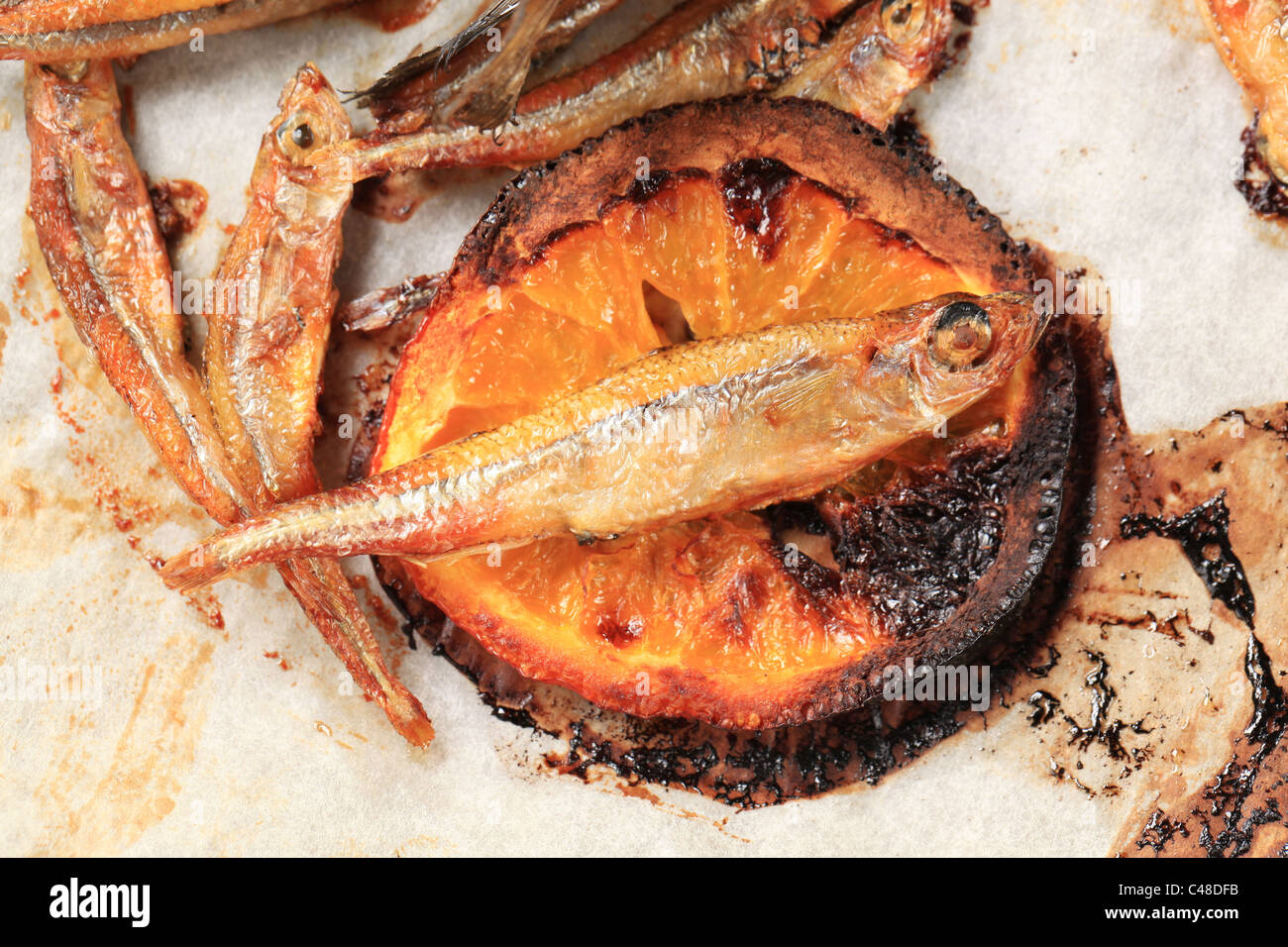 Spicy fried anchovies and slice of lemon - detail - Stock Image