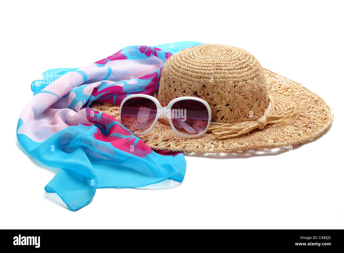 Straw beach hat, sun glasses and shawl isolated on white. Stock Photo