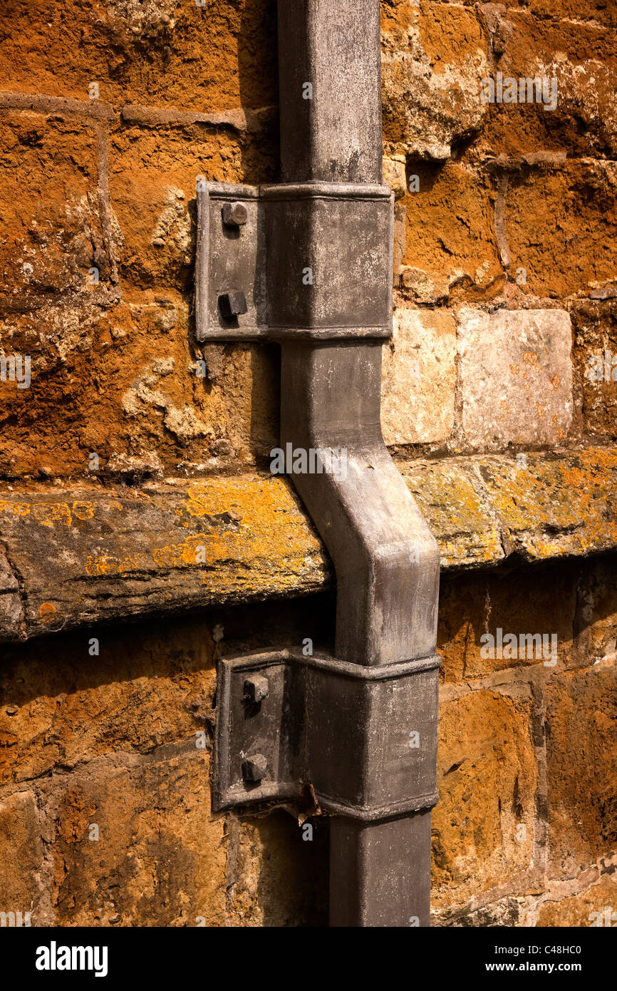 Old lead pipe drainpipe on old rustic wall of St Marys Church, Ashby Folville, Leicestershire, England UK. - Stock Image