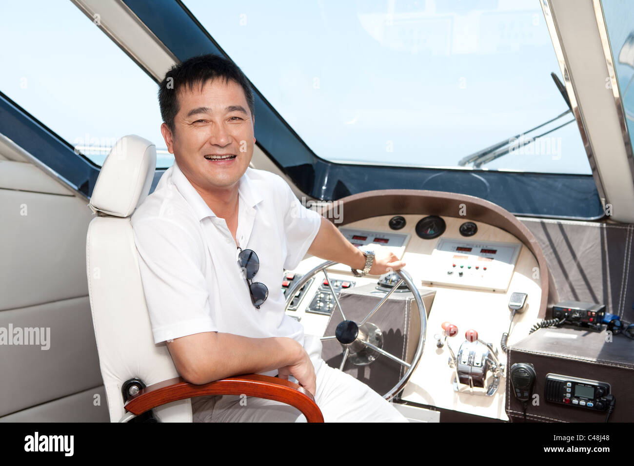 Man in a Yacht Cockpit - Stock Image