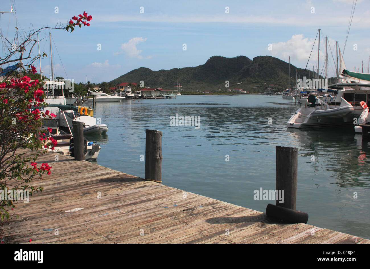 Wooden Jetty, Boats and Hill View, Jolly Bay, Antigua, West Indies - Stock Image