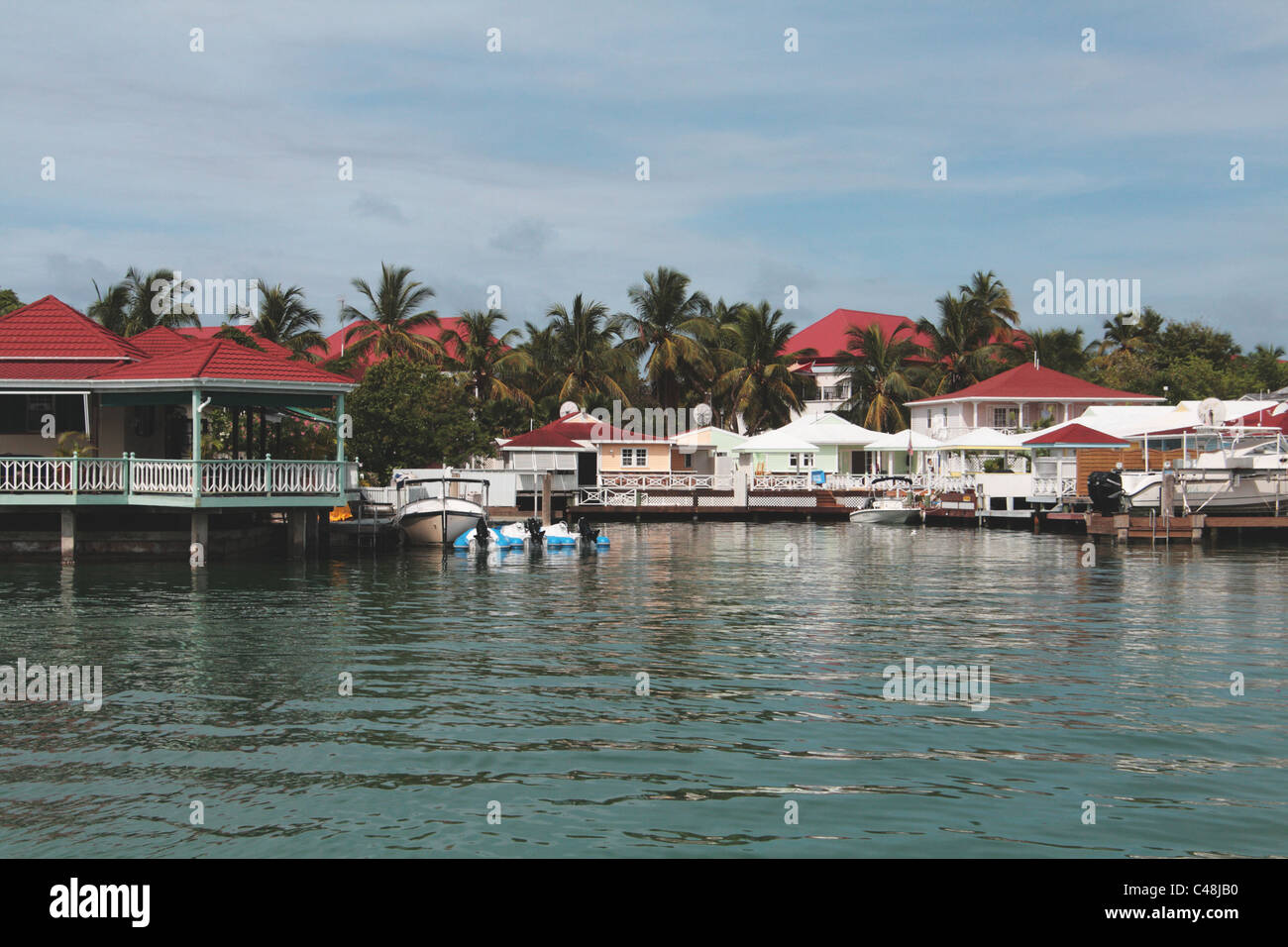 Boats and Water Side Appartments, Jolly Bay, Antigua, West Indies - Stock Image