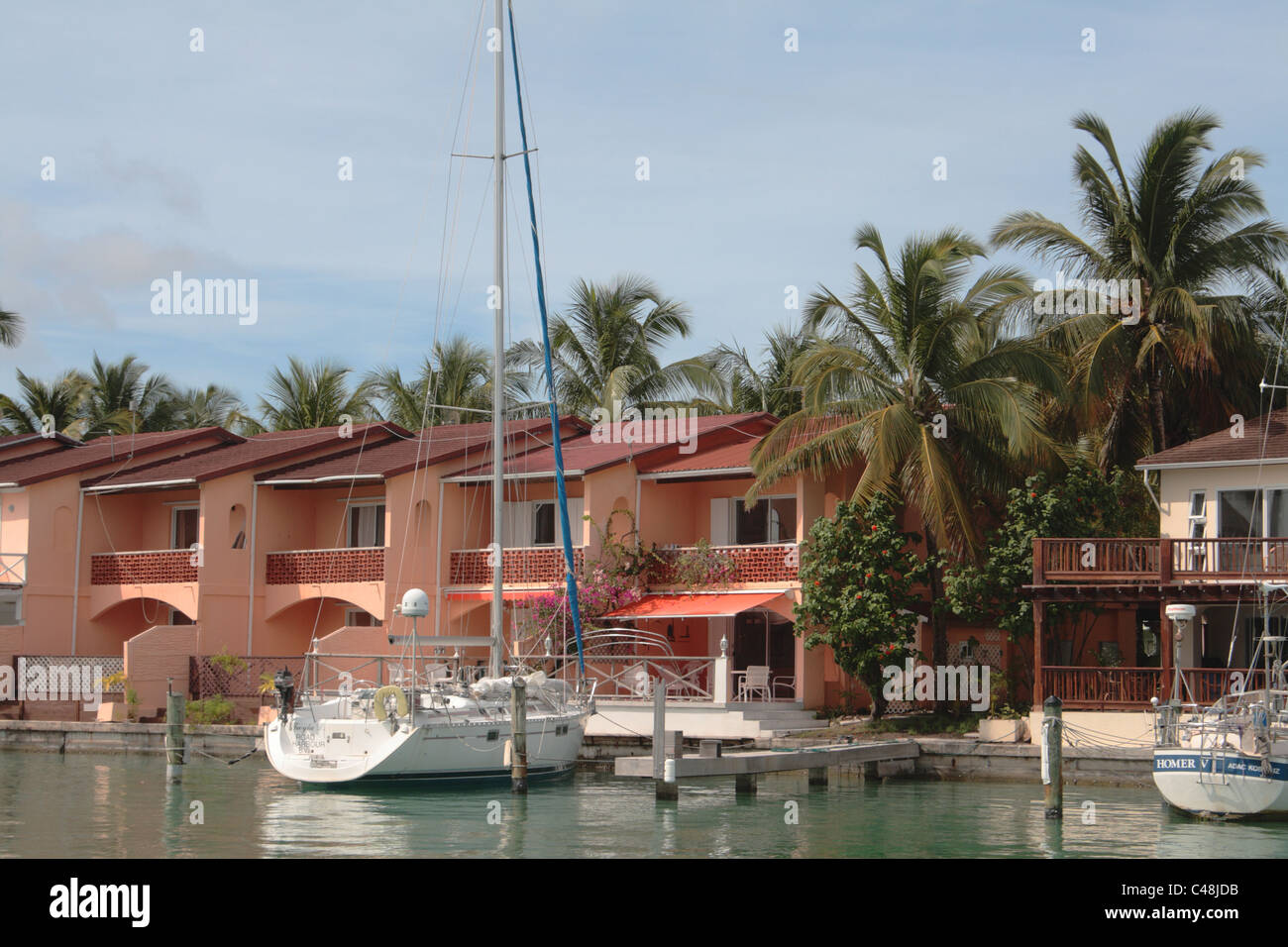 Yacht Moored on Pier in Front of Water Side Appartments, Jolly Bay, Antigua, West Indies - Stock Image