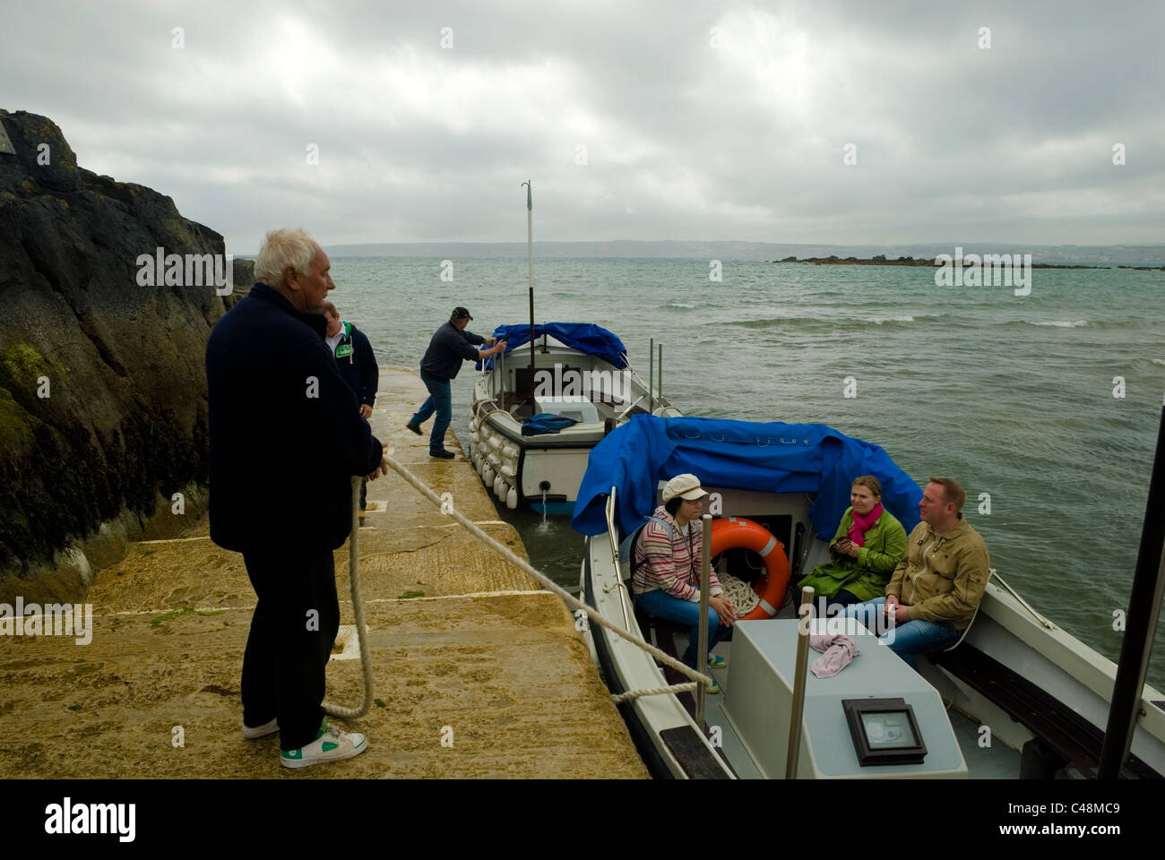 Ferry captains mooring and getting ready to leave for St Michaels Mount, Cornwall England UK - Stock Image