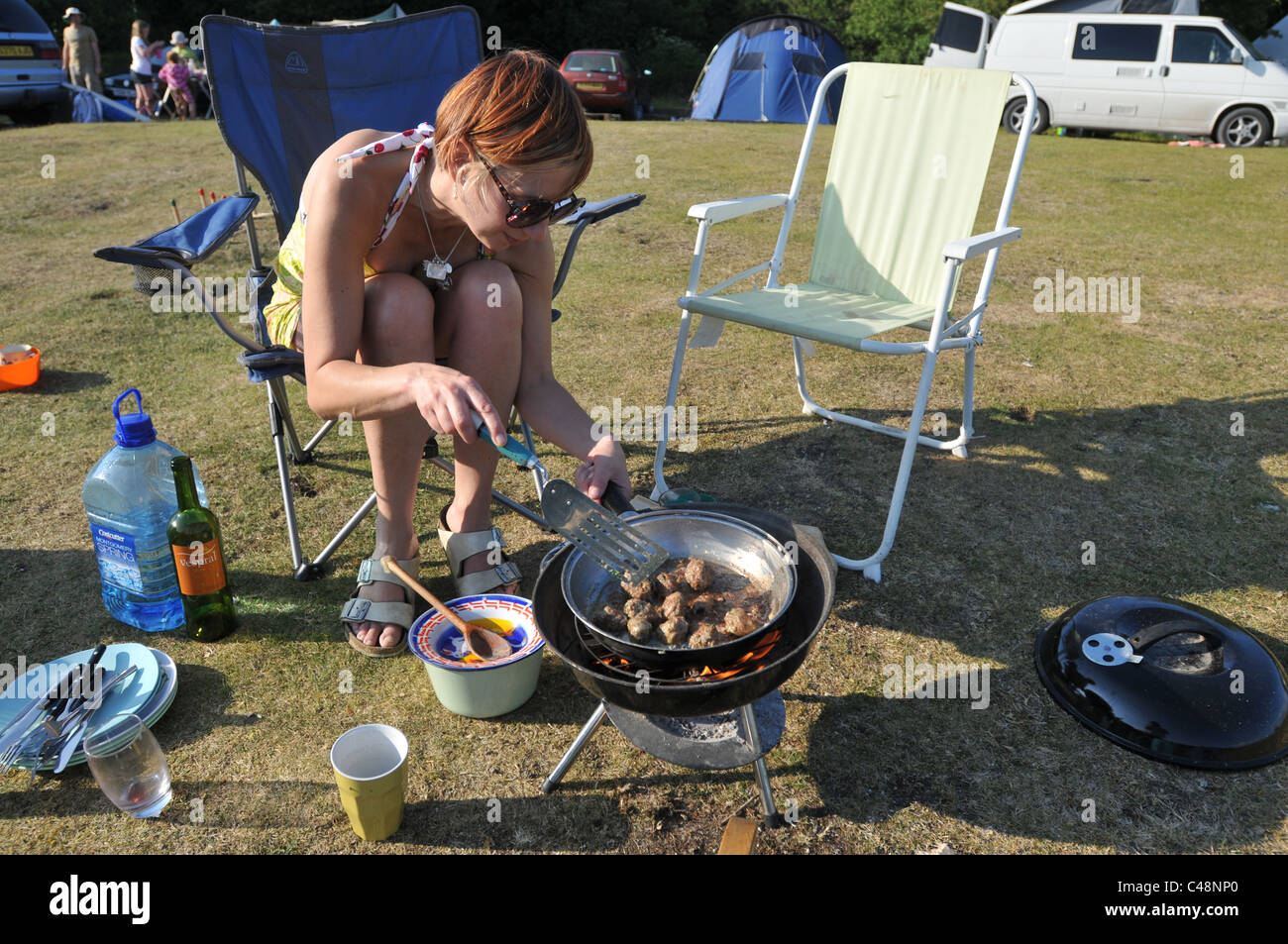 A 45 year old woman cooking on a campsite - Stock Image