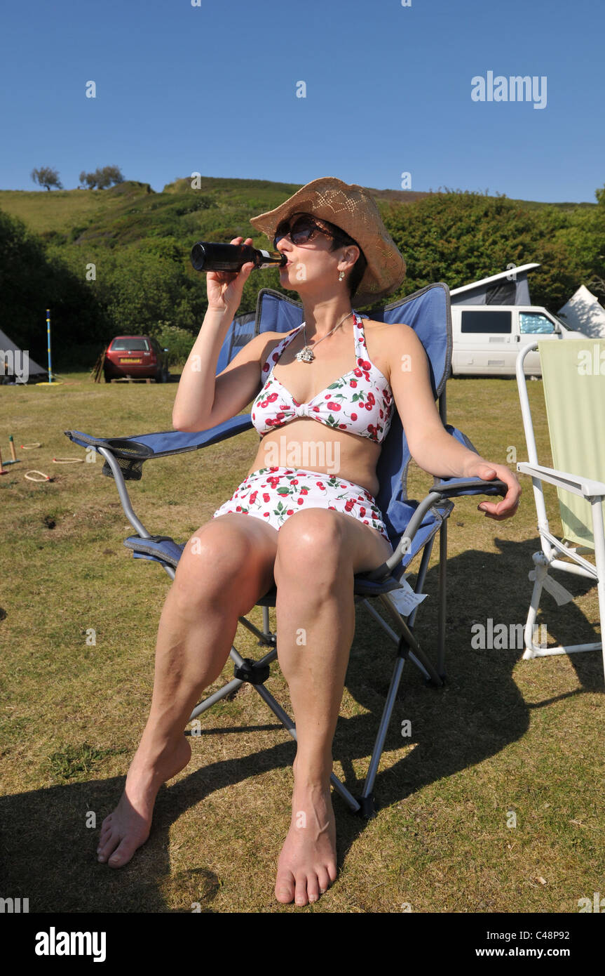 A 45 year old woman drinks beer in the sunshine whilst on a camping holiday - Stock Image