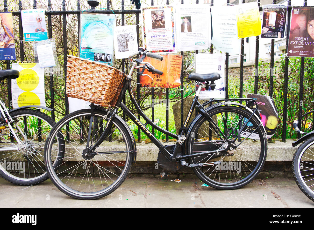 retro bicycle chained to metal rail fence in a cambridge city centre, surrounded by notices and posters - Stock Image