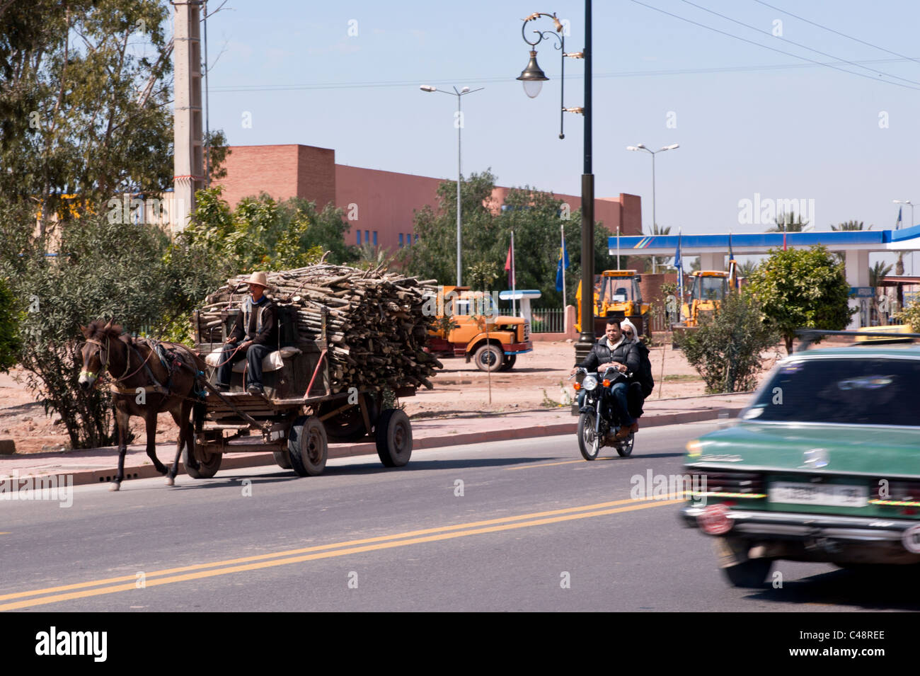 A picture of contrasts in a modernising Morocco from a horse and cart to modern commercial earth movers. - Stock Image