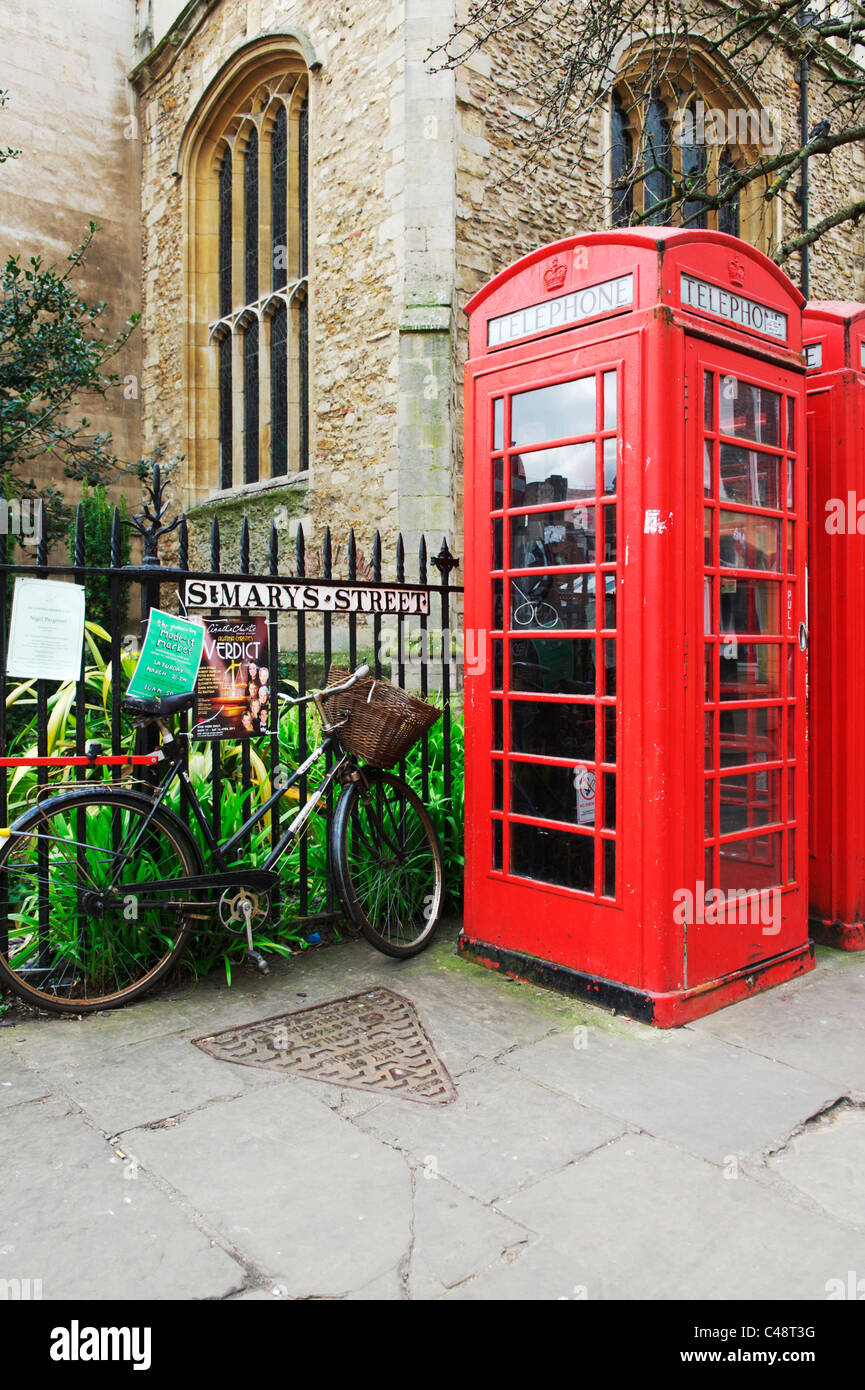 British Telecom red telephone box with a bicycle chained against railings in Cambridge City centre - Stock Image