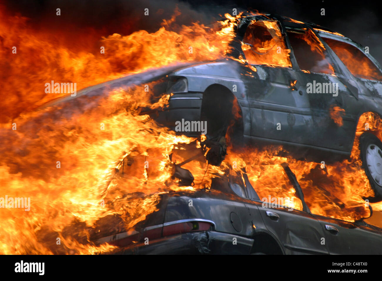 Cars on fire at a blaze in a scrapyard - Stock Image