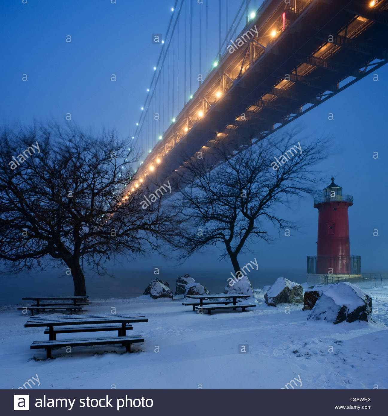 A little red lighthouse sits beneath a large bridge in the snow at dusk. - Stock Image