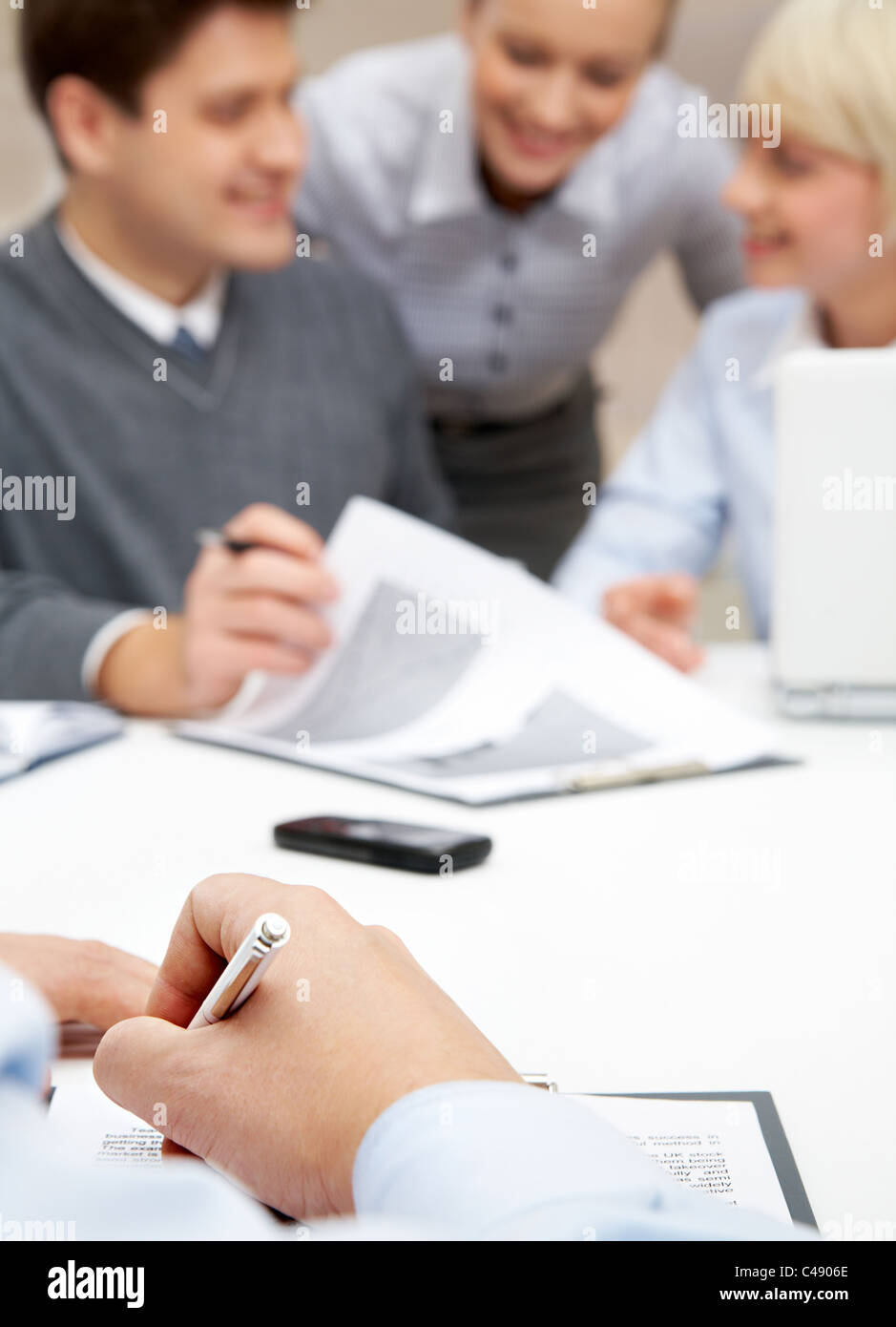 Photo of human hands making notes on background of man explaining idea to employees - Stock Image