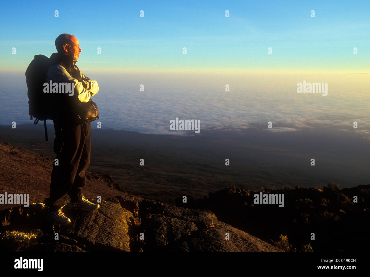 A man stands alone at sunrise as he looks down to the Tanzanian plains below Mount Kilimanjaro. John is attempting - Stock Image
