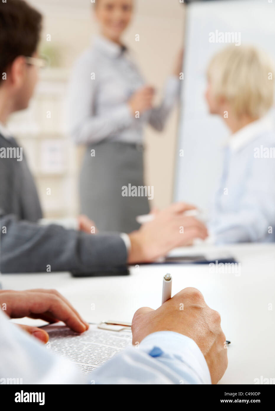 Photo of human hands over workplace on background of smart teacher explaining idea by the board - Stock Image