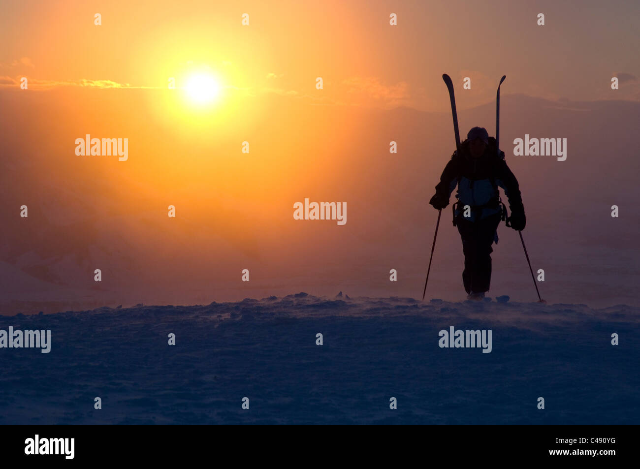 A woman hikes up a mountain with skis on her back at sunrise near Jackson, Wyoming. - Stock Image