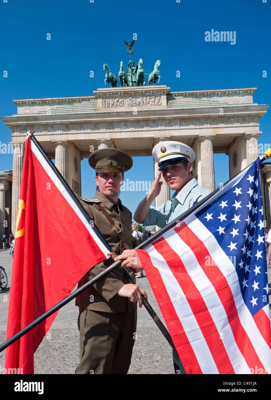 Actors in Soviet and American uniforms posing in-front of Brandenburg Gate in Berlin Germany - Stock Image