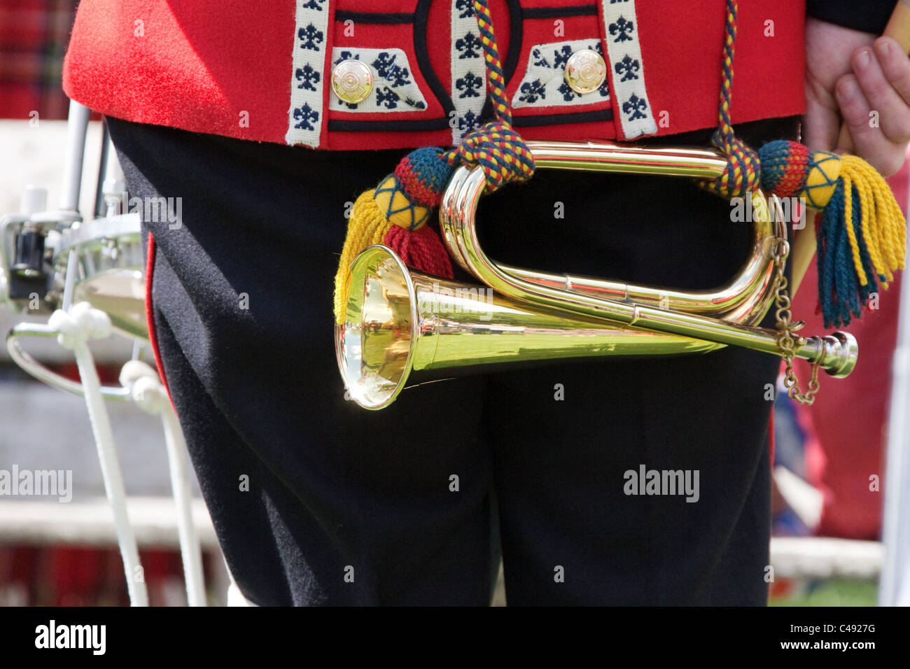 Close-up from the rear of a Scots Guards bandsman showing his bugle glinting in the sunshine. - Stock Image