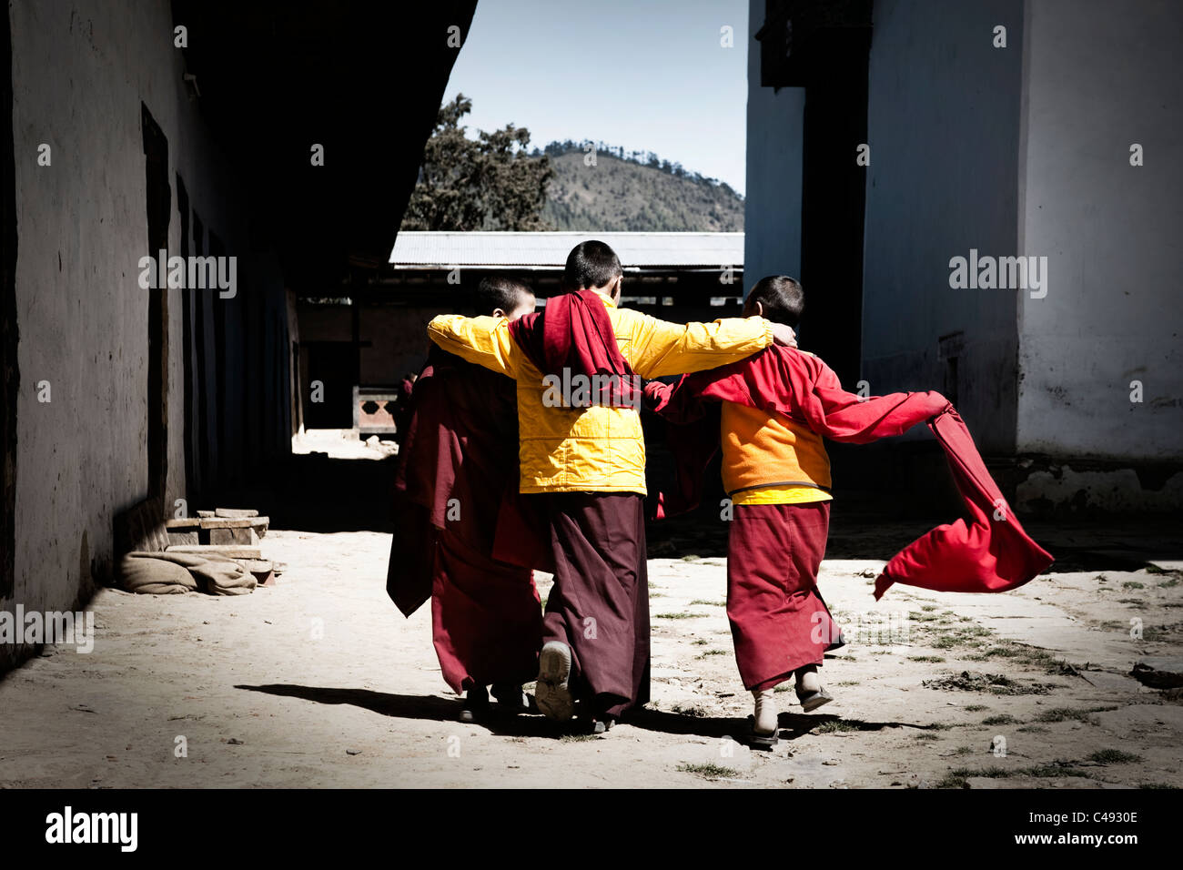 Three young monks walk together outside Gangteng Monastery, near Phobjika Valley, central Bhutan - Stock Image