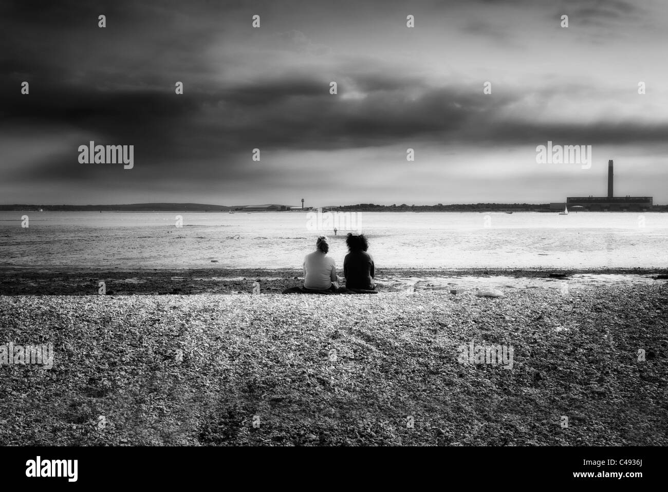 people sitting on a pebble beach at low tide at southampton water UK black & white - Stock Image