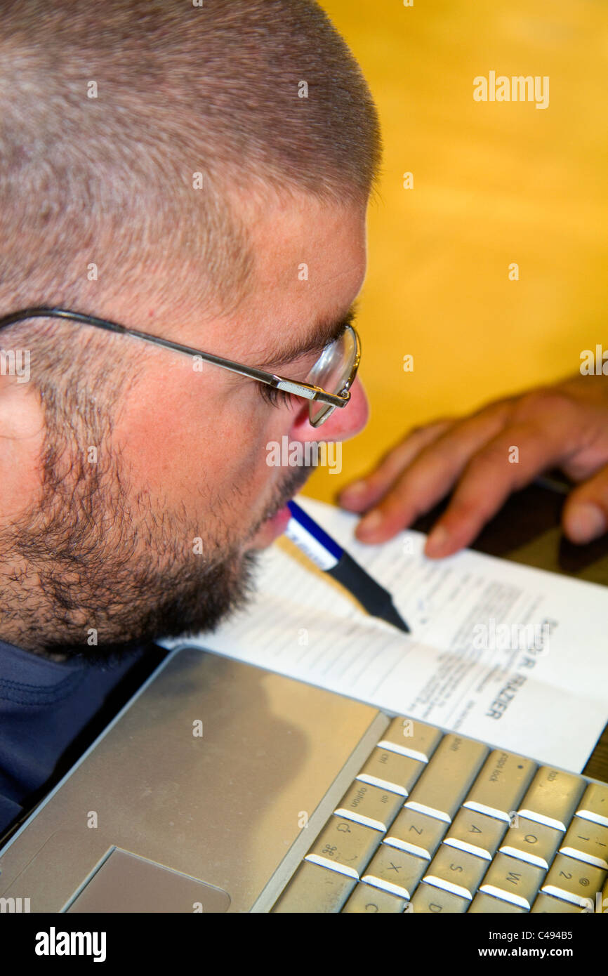 Quadriplegic Argentine man signing his name with his mouth in Buenos Aires, Argentina. - Stock Image