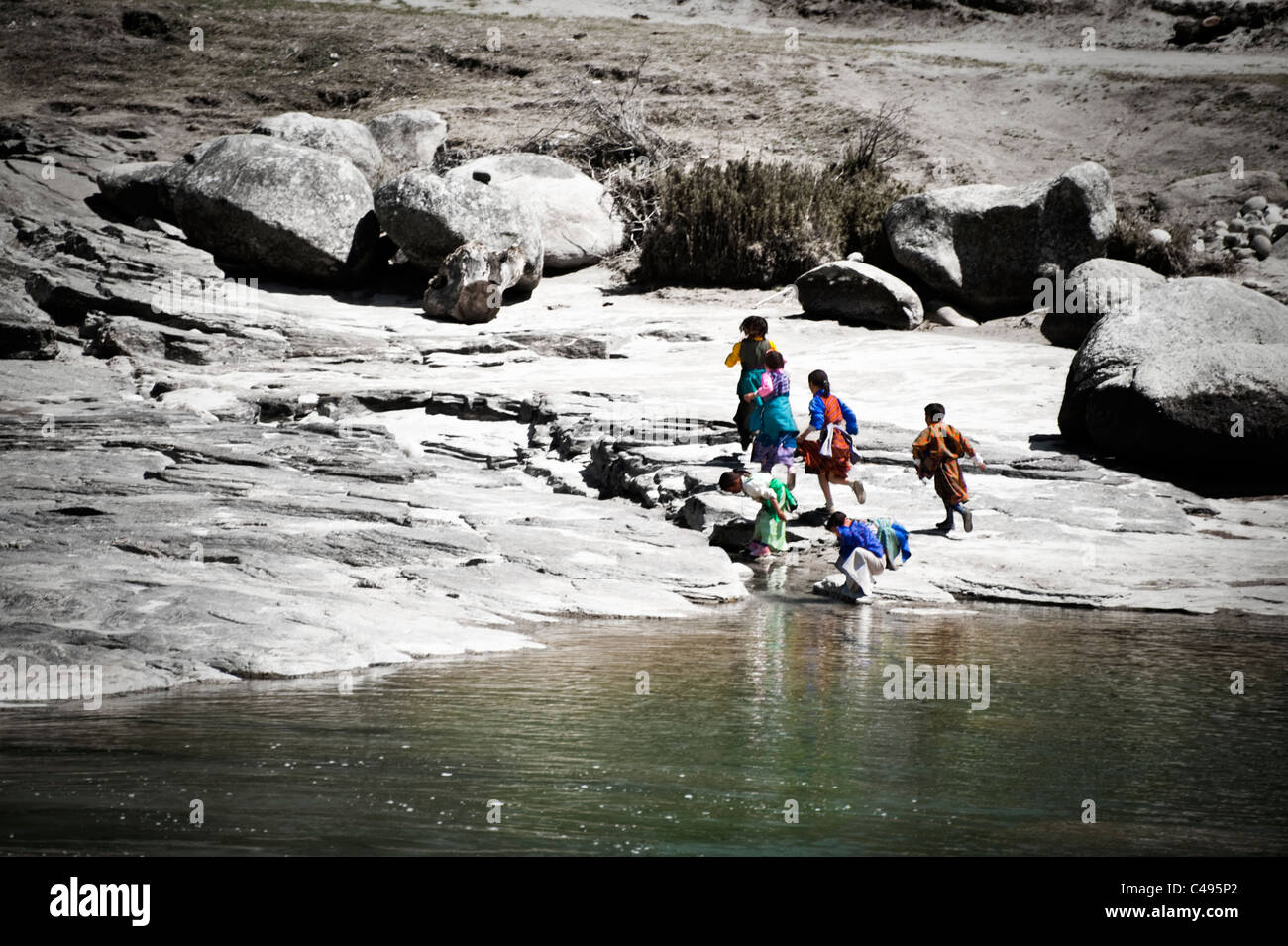 A group of young Bhutanese children run along the river bank, Bhutan - Stock Image