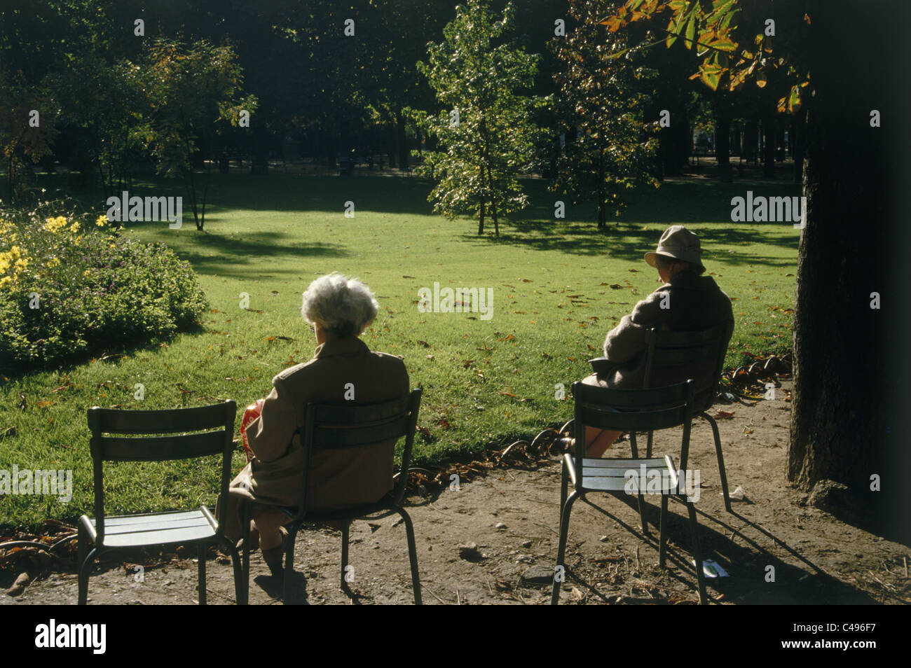 Photograph of two old people csitting in a green park in Paris - Stock Image