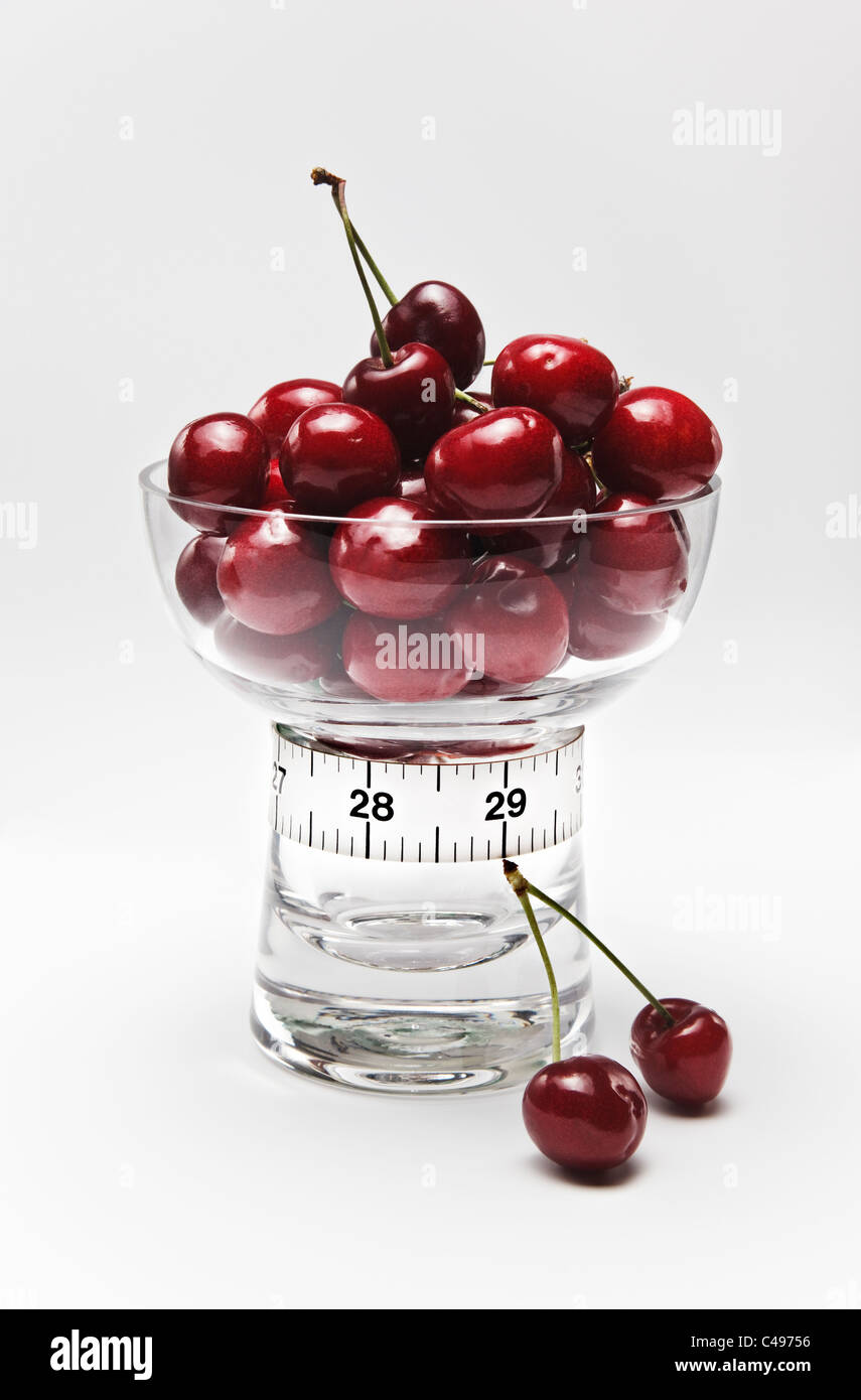 Cherries in Glass Dish and Tape Measure in Inches - Stock Image