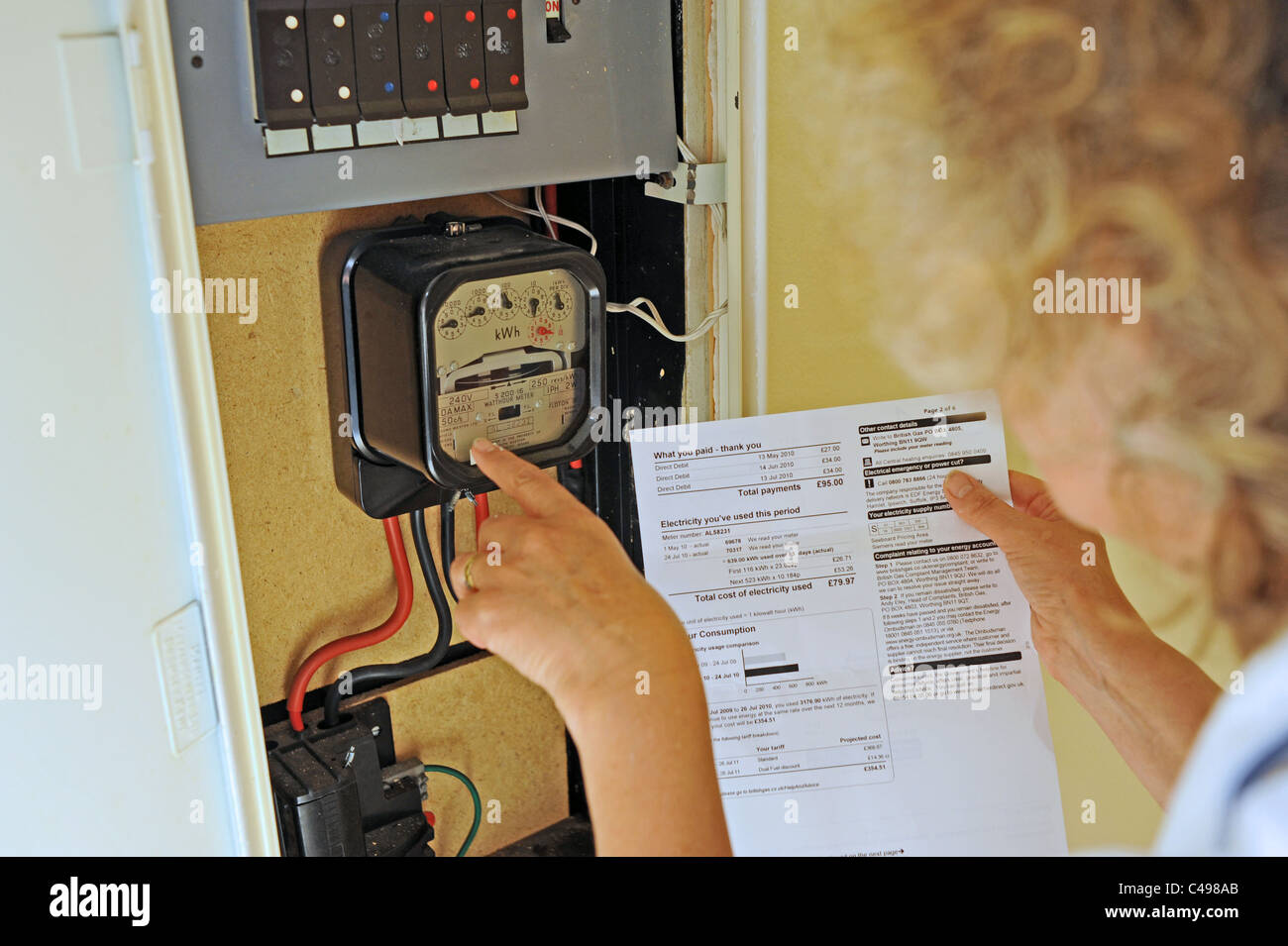Woman contemplating the rising energy prices and bills in the UK as she reads her electricity meter Stock Photo