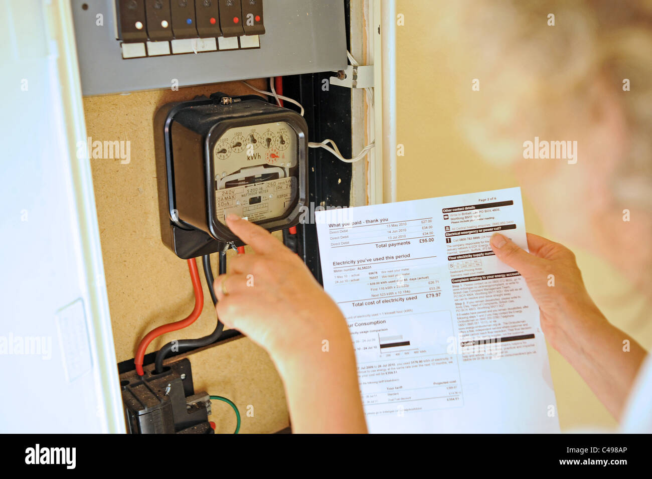 Woman contemplating the rising energy prices and bills in the UK as she reads her electricity meter - Stock Image