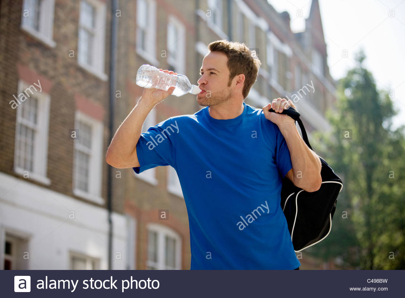 A young man drinking a bottle of water, carrying a sports bag outdoors - Stock Image