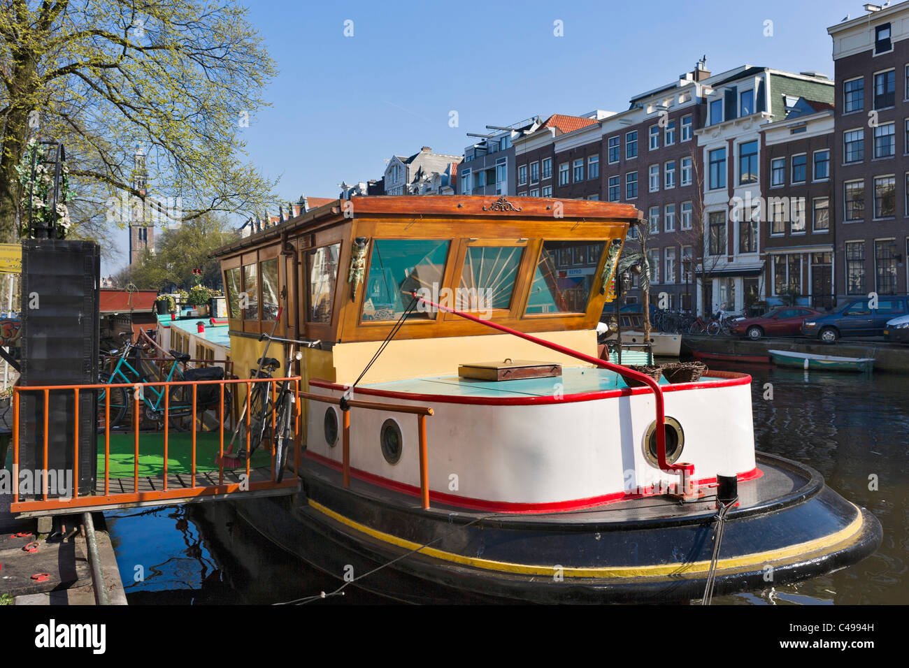 Houseboat on Prinsengracht with the tower of the Westerkerk behind, Grachtengordel, Amsterdam, Netherlands - Stock Image