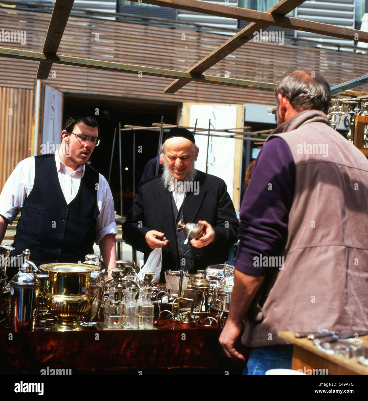 Jewish men making a purchase from a Bermondsey Antiques Market silverware stall holder South London England UK - Stock Image