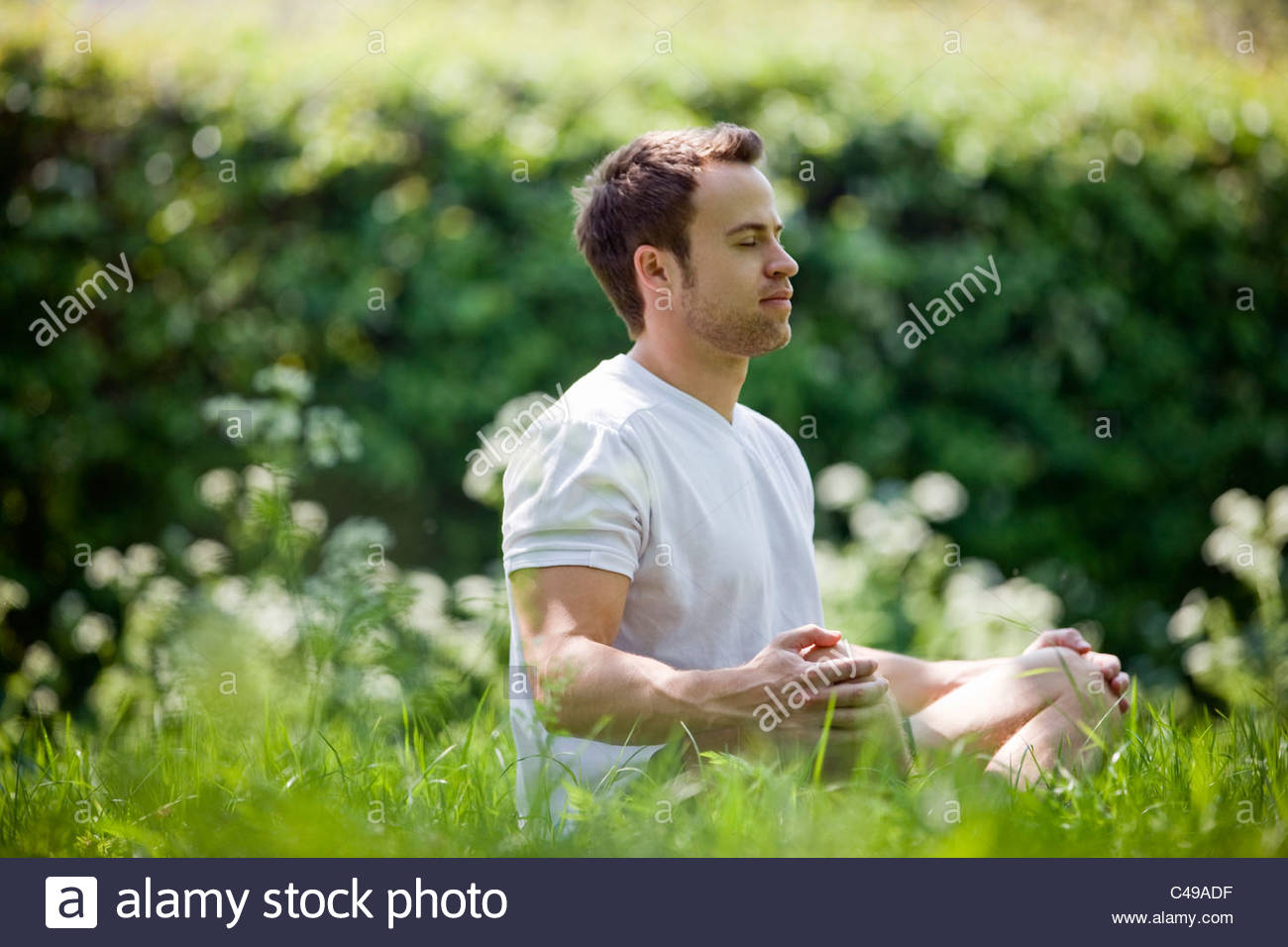 A young man meditating outdoors - Stock Image