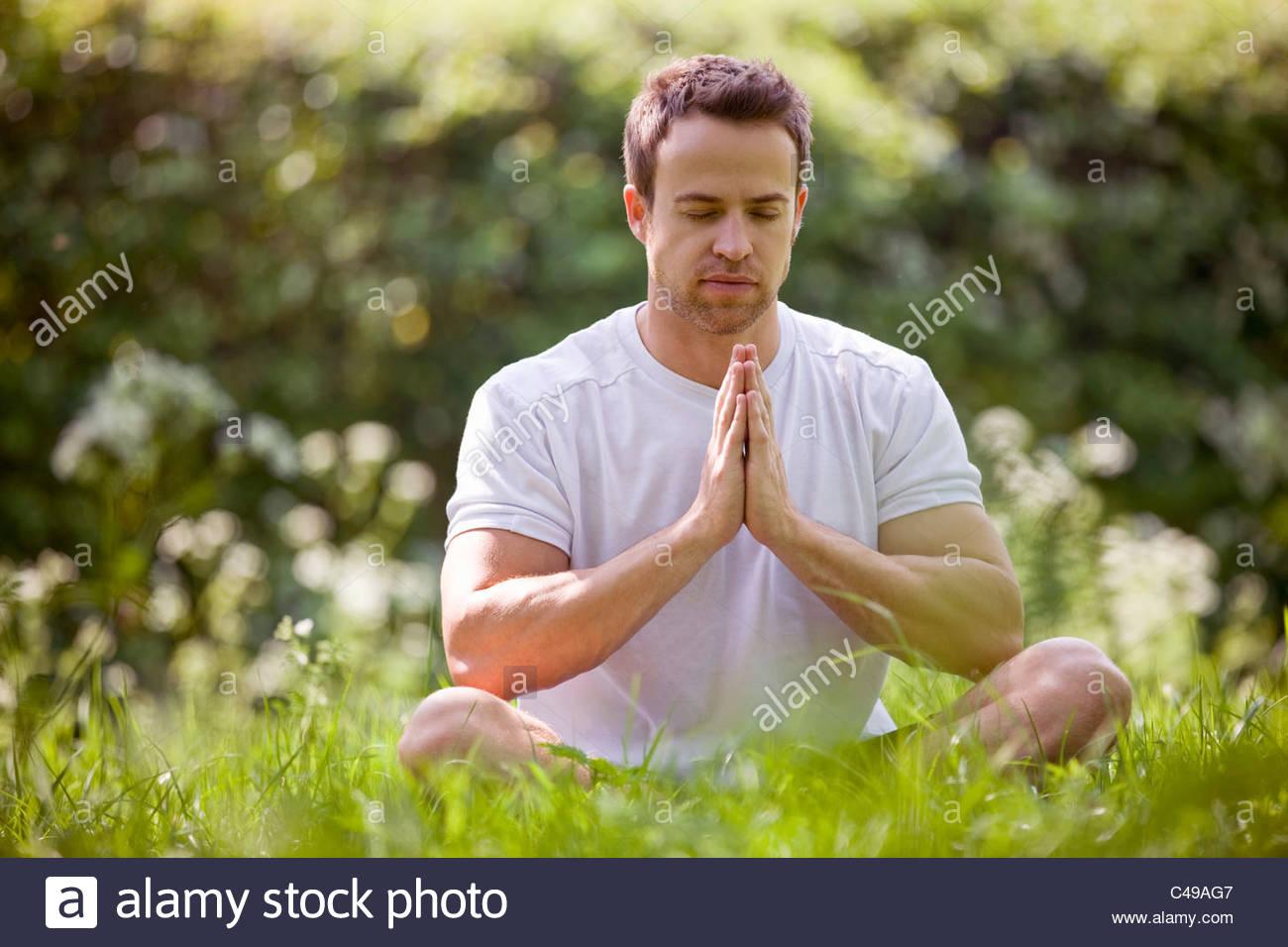 A young man meditating outdoors - Stock Image