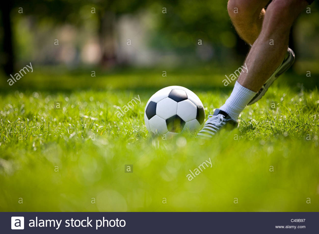 A young man kicking a football outdoors - Stock Image